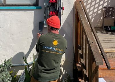 Synergy Team Member installing an electrical panelmaking electrical connections